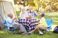 Two senior couples enjoying camping holiday in countryside smiling Stock Photo