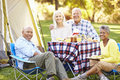 Two senior couples enjoying camping holiday in countryside smiling to camera Stock Images