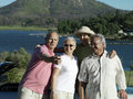 Two senior couples standing beside car near lake man taking photograph with digital camera smiling men Royalty Free Stock Photos