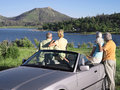 Two senior couples standing beside convertible car admiring view of lake rear view Royalty Free Stock Images
