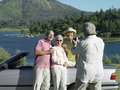 Two senior couples standing beside convertible car near lake smiling man filming with camcorder men Stock Photos
