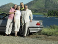 Two senior couples standing beside convertible car near lake smiling portrait Royalty Free Stock Photography