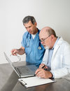 Two senior doctors at laptop computer male talking seriously with Royalty Free Stock Photography