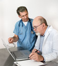 Two senior doctors at laptop computer male talking seriously with Stock Photos