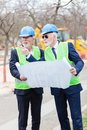 Two senior engineers or businessmen visiting construction site, looking at blueprints and discussing