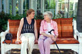 Two senior ladies enjoying a relaxing chat sitting together on wooden bench outdoors in the shade of tree Stock Photos