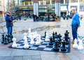 Two senior males play chess outdoors ponder their moves as they on the sidewalk of westlake park in seattle Stock Photos