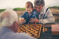 Two senior men having fun and playing chess at park Royalty Free Stock Photo
