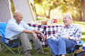 Two senior men relaxing on camping holiday laughing Stock Photos