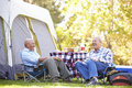 Two senior men relaxing on camping holiday smiling Stock Images