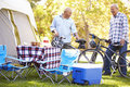 Two senior men riding bikes on camping holiday smiling Stock Photo