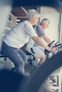 Two senior people working out on elliptical machine. Royalty Free Stock Photo