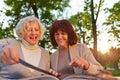 Two senior women reading a cookbook happy in garden Royalty Free Stock Photos