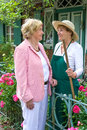 Two Senior Women Talking Together in Garden Royalty Free Stock Photo