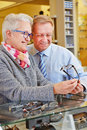 Two seniors buying glasses at happy new optician retail store Royalty Free Stock Photography