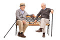 Two seniors playing chess seated on a bench studio shot of game of wooden isolated white background Royalty Free Stock Photography