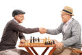 Two seniors shaking hands after a game of chess senior gentlemen playing isolated on white background Royalty Free Stock Photos