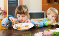 Two serious children eating food