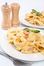 Two servings of homemade pasta carbonara with fresh basil on white background with peppermill and salt shaker Royalty Free Stock Photos