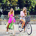 Two sexy girls on a bicycles. Outdoor fashion portrait Royalty Free Stock Photo