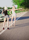 Two sexy girls standing near car and hitchhiking Stock Photos