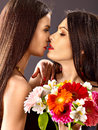 Two sexy lesbian women with flower kissing pink background Royalty Free Stock Photography