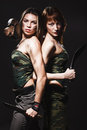 Two sexy women with gun and dagger Stock Image