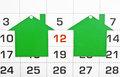 Two shape green houses on a calendar background paying your mortgage on time Stock Photo
