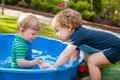 Two sibling boys having fun with water in summer garden on sunny day Royalty Free Stock Photography