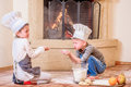 Two siblings - boy and girl - in chef`s hats near the fireplace sitting on the kitchen floor soiled with flour, playing with food