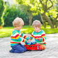 Two siblings, kid boys playing with red wooden toy Royalty Free Stock Photo