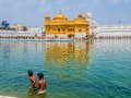 Two sikh boys at golden temple amritsar india march walking in a pool in front of the while tourists and pilgrims entering and Royalty Free Stock Photos