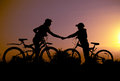 Two silhouette with bicycles at sunset Royalty Free Stock Photo