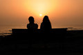 Two silhouetted girls at sunset near the atlantic ocean Stock Photography