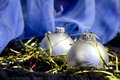 Two silver christmas balls on blue backdrop ornament xmas snow Royalty Free Stock Image