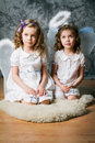 Two sisters with angel wings little in costume Stock Images