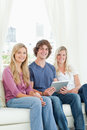 Two sisters and a brother sit on the couch looking at the camera Stock Photos