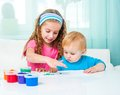 Two sisters draw finger paints at home in bright living room Royalty Free Stock Photos