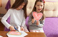 Two Sisters are Drawing Colorful Hearts