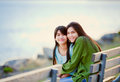 Two sisters friends sitting by lake together happy biracial young girls on bench next to Royalty Free Stock Photo