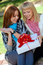 Two sisters with gift in the park Stock Photo