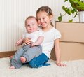 Two sisters moving new house carrying cardboard boxes plant Royalty Free Stock Photos