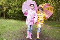Two sisters outdoors with umbrellas smiling Royalty Free Stock Photography