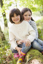 Two sisters outdoors in woods sitting on log Royalty Free Stock Photos
