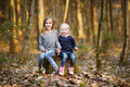 Two sisters picking the first flowers of spring little on sunny evening Stock Photography