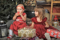 Two sisters in red dresses baby with presents Royalty Free Stock Photo