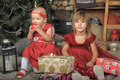 Two sisters in red dresses baby with presents Royalty Free Stock Image
