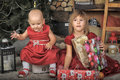 Two sisters in red dresses baby with presents Stock Photo
