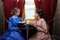 Two sisters in retro dress reading books in train compartment Royalty Free Stock Photo