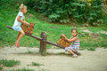Two sisters ride on swings against summer nature Royalty Free Stock Photography